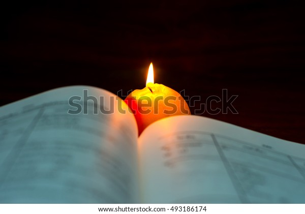 Open book and apple candles burn in the darkness