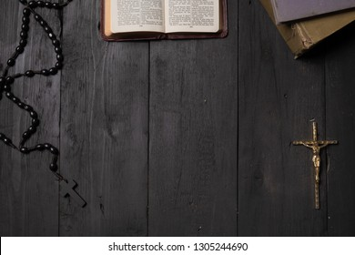 Open book of Bible and crucifix on dark table, top view. Flat lay image of New Testament, cross and rosary on old black background