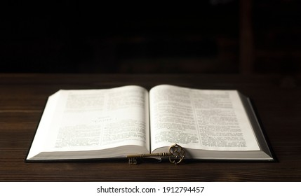 Open book Bible. Old antique key. On a wooden table.