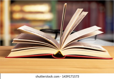 Open book and black glass on bokeh background