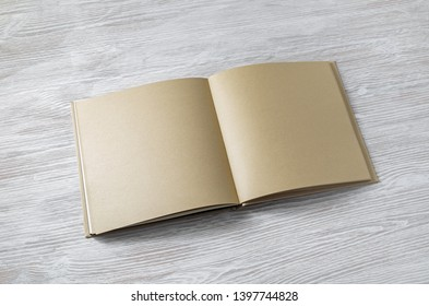 Open book with blank craft paper pages on light wooden background.
