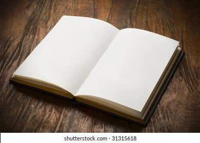 an open book with blank pages on wood table