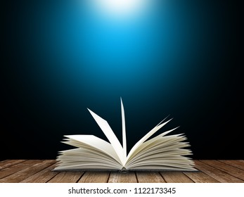 Open book with blue light on black background