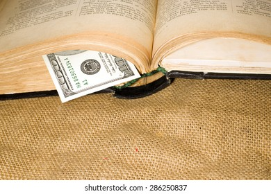 Open book with a bookmark from USD 100 on sacking