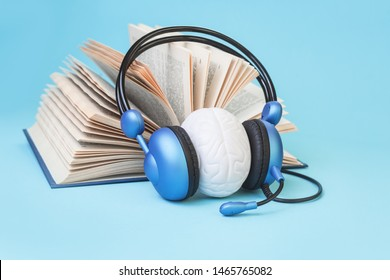 Open book and brain in headphones on blue. Listening practice or test, audio books dyslexia reading difficulty and disorder and auditory memory concept. Education and neurology with copy space