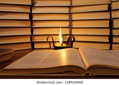 Open book and a burning candle. Lighted candle in an old candlestick on a books background. Reading a book by candlelight