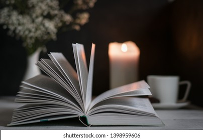 An open book and a burning candle on the table, dark photo