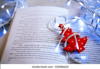 Open book, Christmas decor and garland, closeup