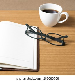 open book with coffee cup on wood background