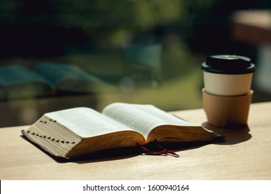 Open book with cup of coffee on wooden desk beside the window