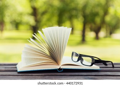 Open book and eyeglasses on a bench in park in a sunny day, reading in the summer, education, textbook, back to school concept
