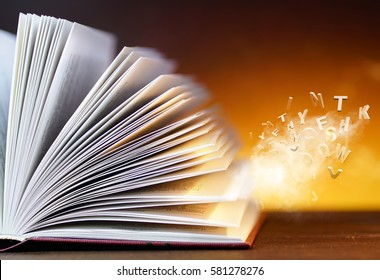 Open book with flying letters with a beauty magical glow on golden warm background. Concept border template for education, imagination, research, reading, mystery, daydreaming, sorcery .
