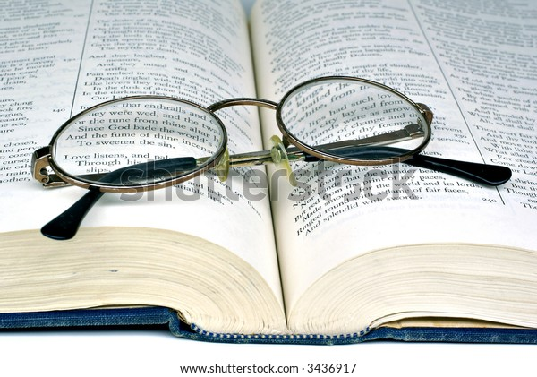 Open book with folded reading glasses on white background
