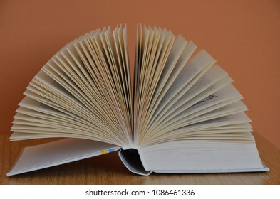 Open Book forming a fan on wooden Table