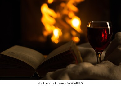 Open book with glass of wine in front of fireplace
