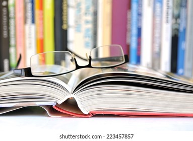 Open book with glasses, multicolored books in background