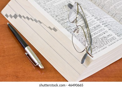 Open book with glasses on pages and pen