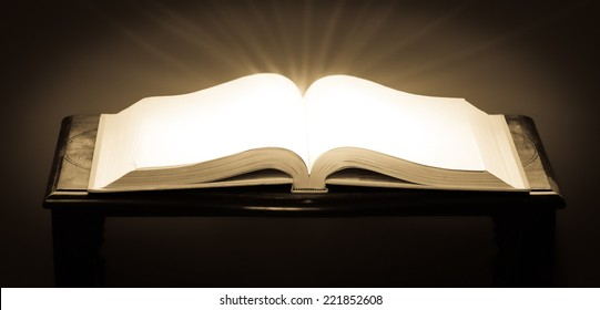 An open book with glowing blank pages and light rays coming from the pages with trendy processing