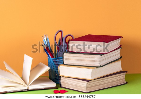 Open book, hardback books and magnifying glass on bright colorful background. Back to school. Copy space for text