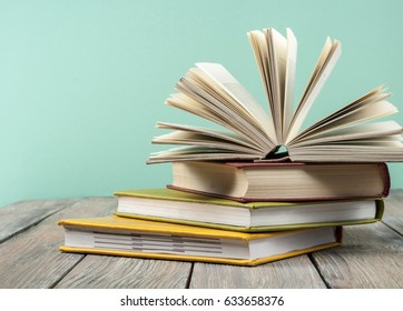 Open book, hardback books on wooden background. Back to school. Copy space for text. Education concept.
