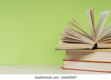 Open book, hardback books on wooden table on the background of green wall. Copy space for text.Education concept.