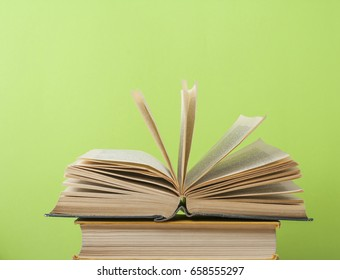 Open book, hardback books on wooden table on the background of green wall. Copy space for text. Education concept.