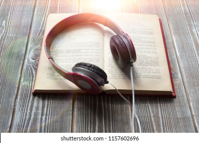 open book, headphones on the background of a wooden table education.