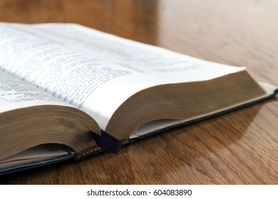 Open book Holy Bible on yellow wooden background