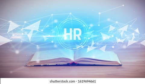 Open book with HR abbreviation, modern technology concept
