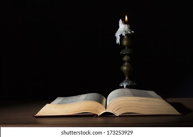 open book illuminated by candle in retro candlestick