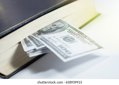 Open book isolated on white background with money in it.