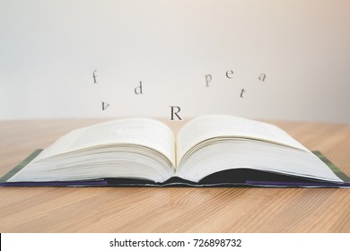 An open book with letters floating above it on a wooden table or desk. White wall in the background.