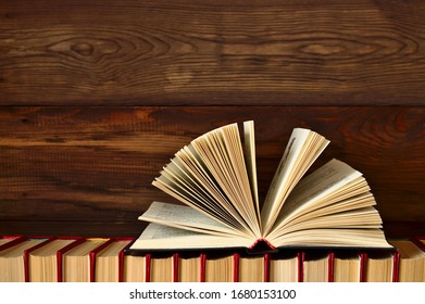 An open book lies on a stack of books on a wooden background. Copy space.
