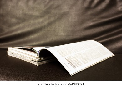 Open book magazine stack on leatherette background. (selective focus )