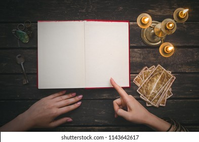 Open book of magic with blank pages and tarot cards on fortune teller table background. Futune reading concept. Divination.