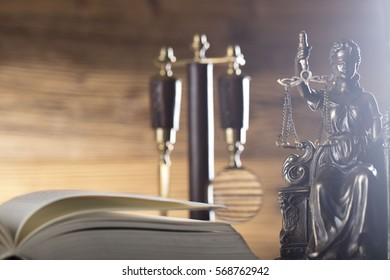 open book, magnifying glass, books, scales of justice, gavel, statue of justice, brown background, wooden table