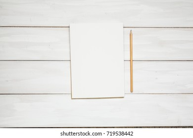 Open book or note and pencil on wooden white plank background. Top view with copy space.