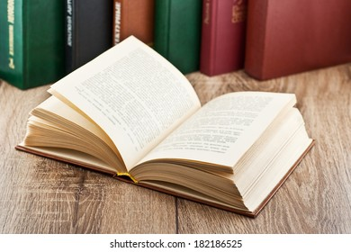 open book on background of several books