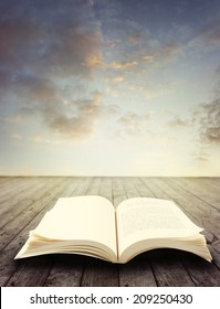 Open book on deck in front of sky