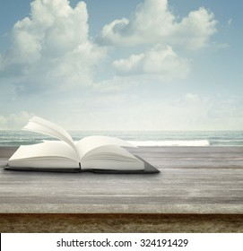 Open book on deck in front of blue sky and sea