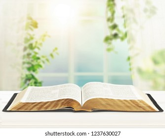 Open book on old wooden table.