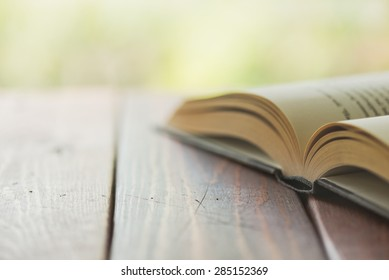 An open book on a rustic wooden table with nature in the background - Split toned