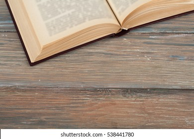 An open book on a rustic wooden table, copy space for ad text. Available in high-resolution and several sizes to fit the needs of your project.