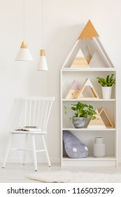 Open book on a simple, wooden chair and a bookcase with plants and DIY mountains decorations in a white, scandinavian living room interior
