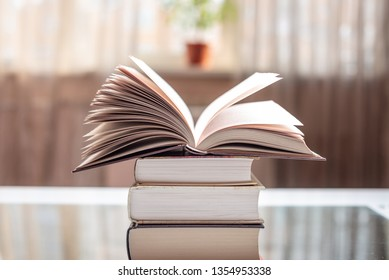 An open book on a stack of books on a table in a bright room. Education and reading of paper books. Exam preparation in schools and colleges