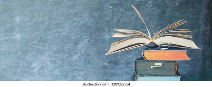 Open Book on a stack of old books in front of a blackboard, panoramic format, good copy space