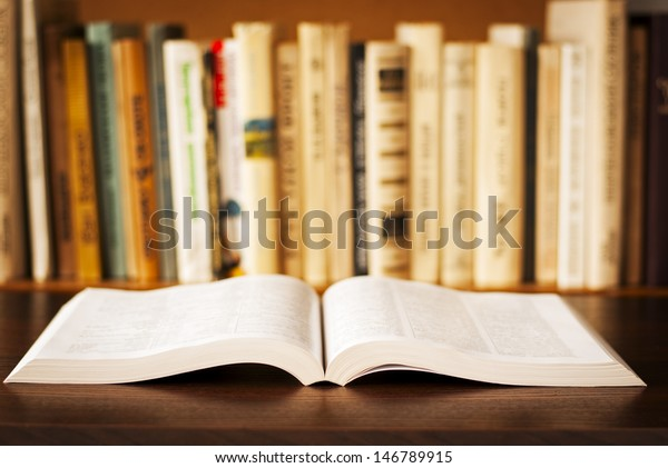 open book on the table and a bookshelf in the background