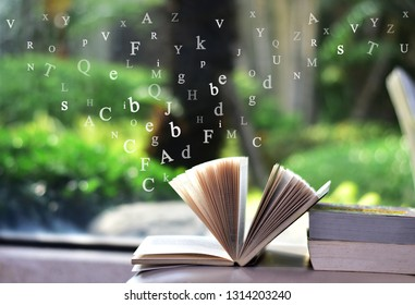 Open book on the table and English alphabet Floating above the book
