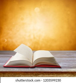 Open book on table in front of orange blurred background