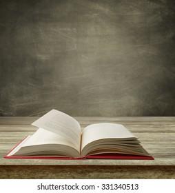 Open book on table in front of blackboard
